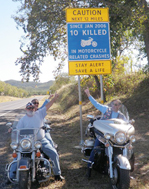 "While seated on their motorcycles, three drivers point to the new motorcycle sign ""Caution Next 12 Miles. Since Jan 2006 10 Killed in Motorcycle related crashes. Stay Alert. Save a life.""s."